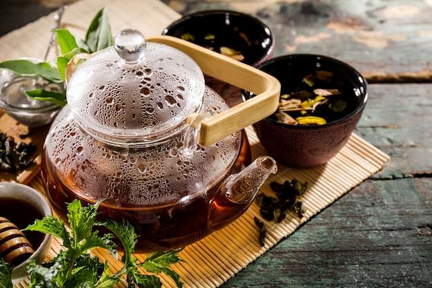 Tè verde fresco gustoso nella ceramica di teiera di vetro sulla vecchia tabella rustica