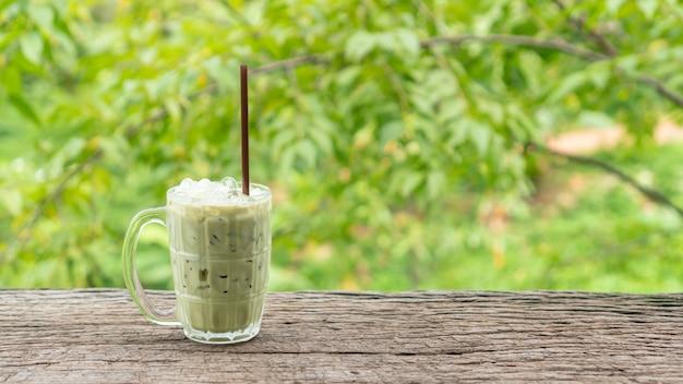 Tè verde ghiacciato su una tavola di legno e su una natura verde