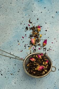 Tè verde in foglie per la preparazione in un setaccio con boccioli di rosa essiccati