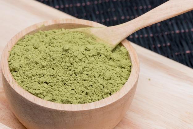 Tè verde in polvere in tazza di legno.