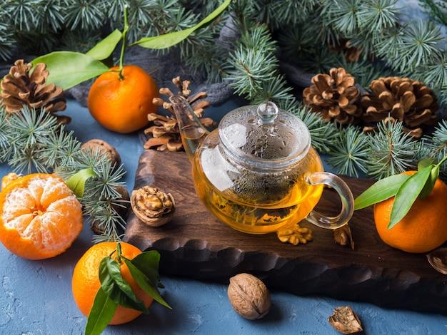 Tè verde in vaso di vetro e mandarini - natura morta di inverno