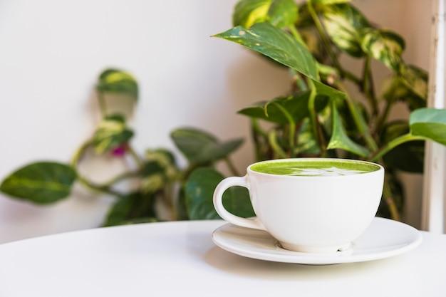 Tè verde matcha caldo in tazza sul piattino sul tavolo bianco