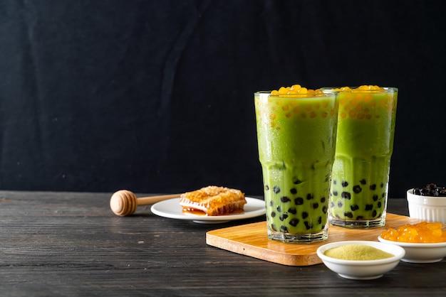Tè verde matcha latte con bolle e bolle di miele