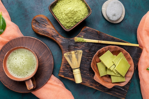 Tè verde matcha, polvere e cioccolato su fondo verde smeraldo. vista dall'alto.