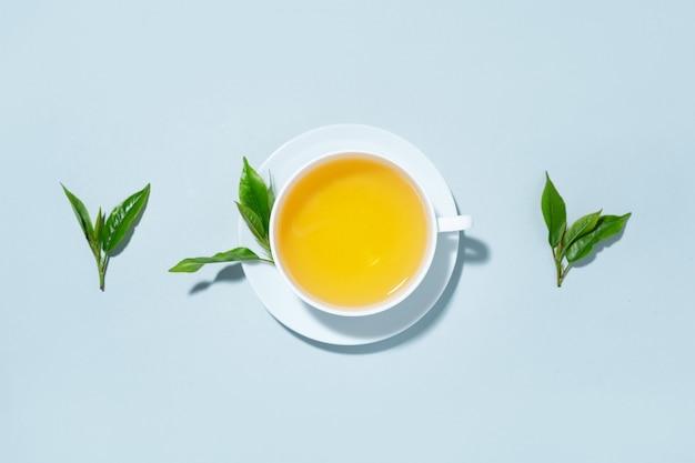Tè verde preparato in tazza con foglie di tè su sfondo blu pastello. vista dall'alto.