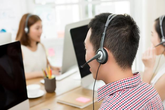 Team di agenti del servizio clienti asiatico di telemarketing,