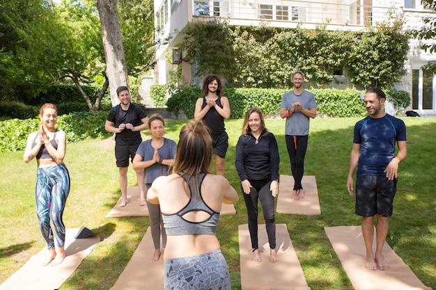 Team di amanti dello yoga che terminano le lezioni