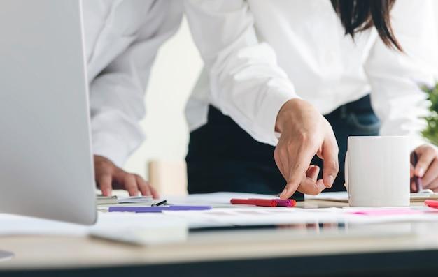 Team di analisti aziendali che discutono la strategia aziendale nella moderna sala ufficio.