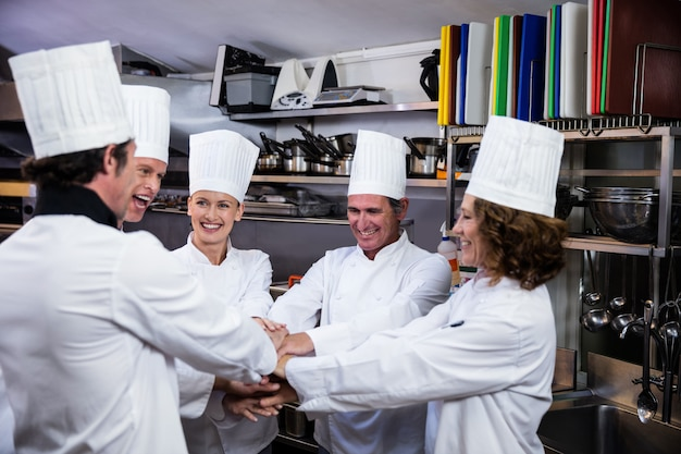 Team di chef che uniscono le mani e incoraggiano