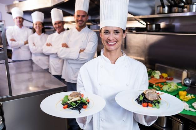Team di chef con uno che presenta piatti