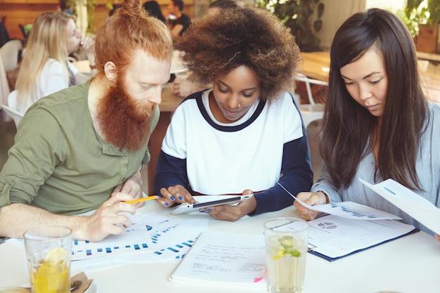 Team di esperti di marketing che sviluppano la strategia aziendale al caffè donna africana che presenta il piano aziendale al suo partner con la barba rossa sulla tavoletta digitale mentre il loro collega asiatico analizza i grafici