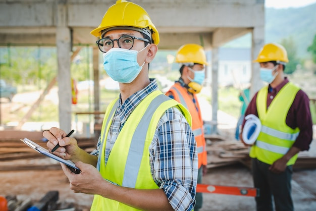Team di ingegneri edili e tre architetti sono pronti a indossare maschere mediche. corona o covid-19 indossano maschere durante la progettazione della costruzione.