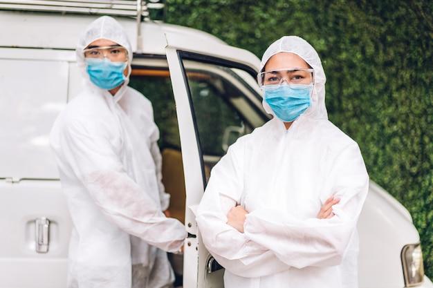 Team di professionisti per la disinfezione dei lavoratori in maschera protettiva e tuta bianca disinfettante spray per la pulizia dello spray per il servizio di assistenza uccidere il coronavirus a casa del cliente