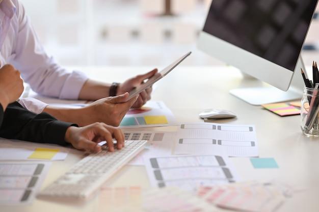 Team di progettisti di ux che utilizza tablet progettando il layout del telefono cellulare web di wireframe