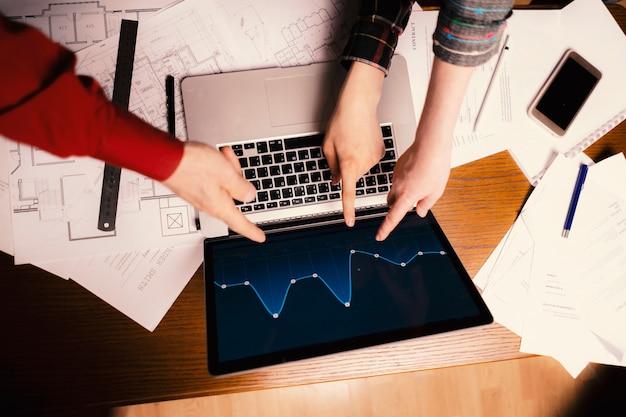 Team di uomini d'affari di talento puntano sul grafico nel laptop
