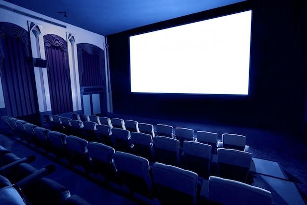 Teatro del cinema che mostra lo schermo di film bianco vuoto.