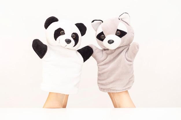 Teatro delle marionette su uno sfondo bianco. gli animali amichevoli si tengono per mano. il concetto di giocare con i bambini, l'amicizia, la famiglia, l'intrattenimento. la tata intrattiene i bambini. copyspace
