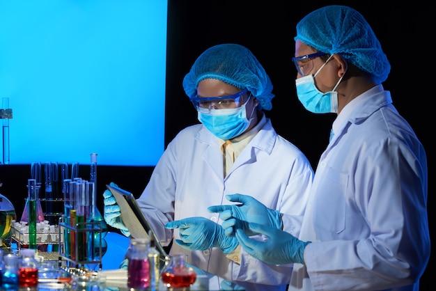 Tecnici di laboratorio che discutono i dettagli della ricerca