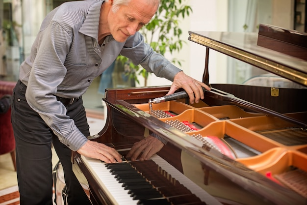Tecnico anziano dello strumento musicale che sintonizza una tastiera di piano.