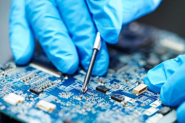 Tecnico asiatico che ripara il computer del circuito principale.