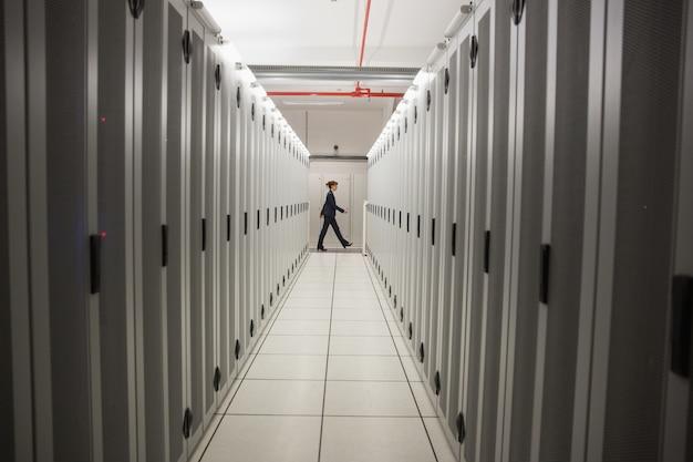 Tecnico che cammina nel corridoio del server