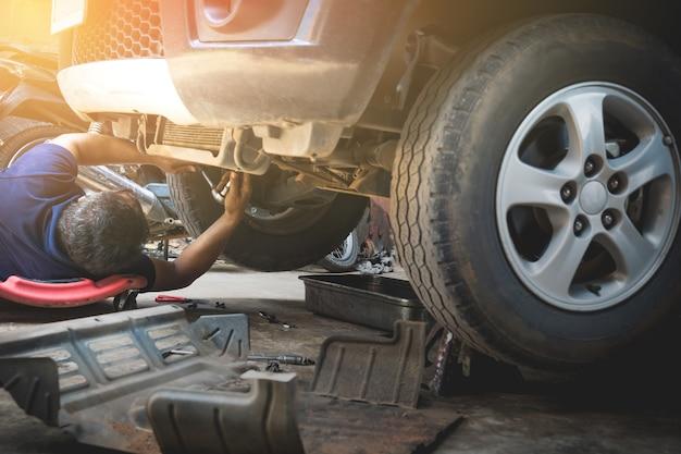 Tecnico che controlla il motore dell'automobile. meccanico auto che controlla il motore di automobile
