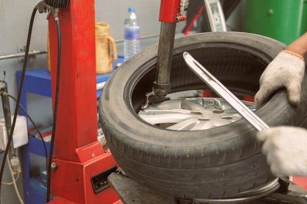 Tecnico che rimuove la gomma dal disco della ruota dell'automobile e che equilibra la gomma sull'equilibratore nel garage di riparazione automatica
