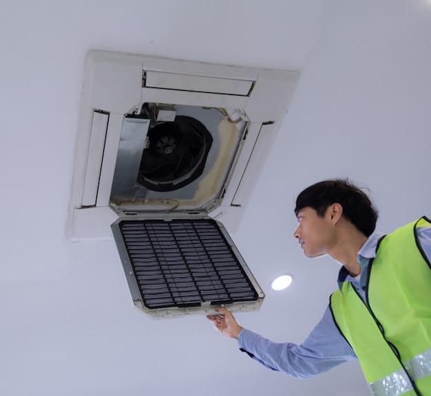 Tecnico che ripara il condizionatore d'aria sulla parete.
