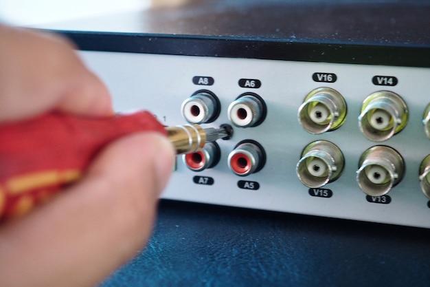 Tecnico che ripara l'attrezzatura video di cctv dvr (digital video recorder)