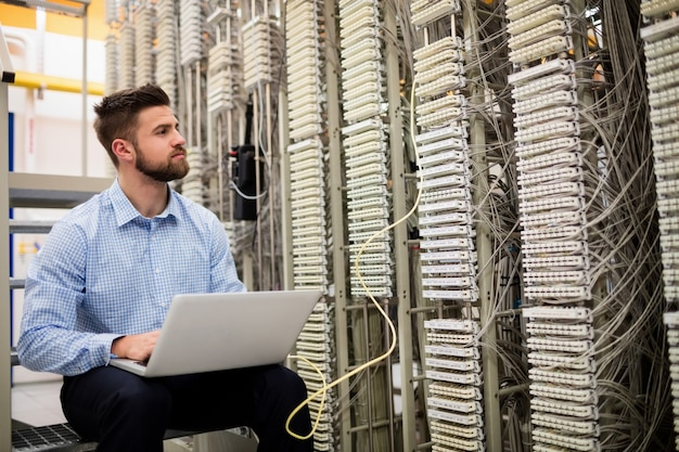 Tecnico che utilizza computer portatile mentre analizzando server