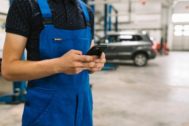 Tecnico che utilizza il telefono all'officina dell'automobile