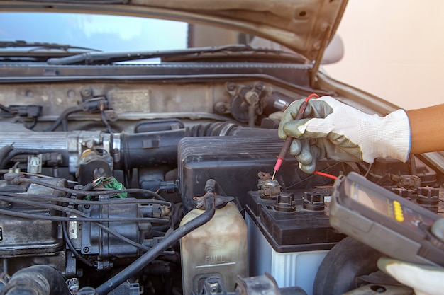 Tecnico che utilizza strumenti di misurazione per controllare la batteria dell'auto. concetti di servizio di riparazione auto e assicurazione auto.