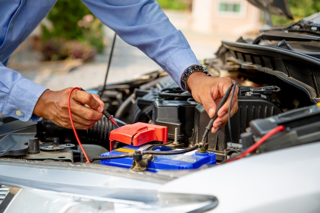 Tecnico che utilizza strumenti di misurazione per controllare la batteria dell'auto.