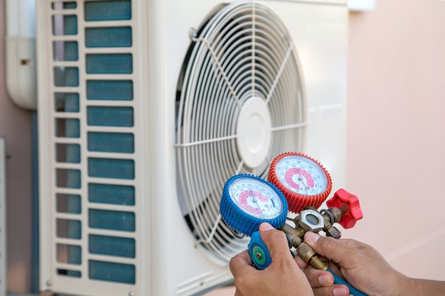 Tecnico che utilizza strumenti di misurazione per riempire i condizionatori d'aria e controllare l'unità del compressore d'aria esterno