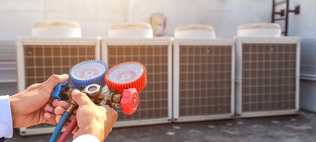 Tecnico che utilizza strumenti di misurazione per riempire i condizionatori d'aria.