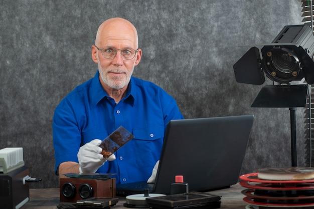 Tecnico con i guanti bianchi che digitalizzano la vecchia fotografia sulla lastra di vetro