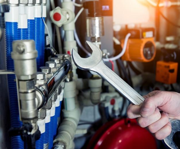 Tecnico del riscaldamento che ripara il sistema di riscaldamento moderno nel locale caldaie. centralina automatica