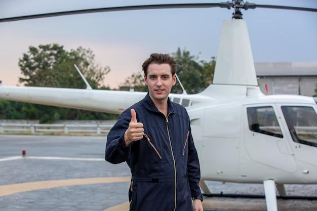 Tecnico dell'elicottero che sta contro l'elicottero in aeroporto