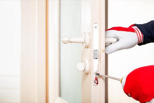Tecnico fixing lock in door with screwdriver. servizio di blocco delle porte concept.