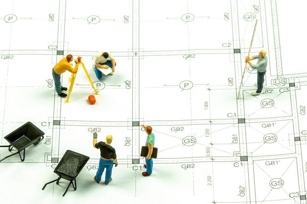 Tecnico geometra persone in miniatura sta misurando la distanza per costruire una casa.