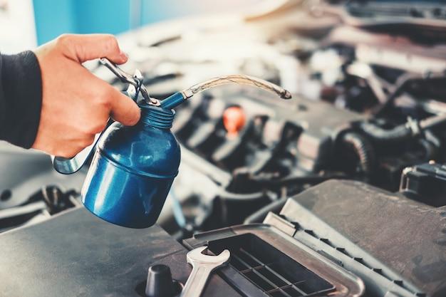 Tecnico hands del meccanico di automobile che lavora in automobile di servizio e manutenzione di riparazione automatica