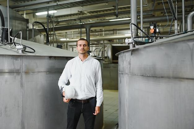 Tecnico industriale maschio felice all'interno di una fabbrica
