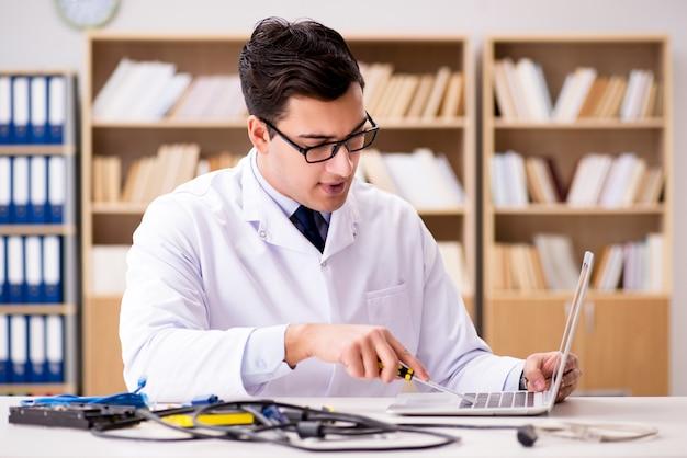 Tecnico informatico che ripara il computer portatile rotto del computer portatile