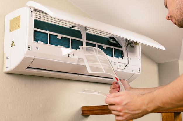 Tecnico maschio pulizia condizionatore d'aria al chiuso