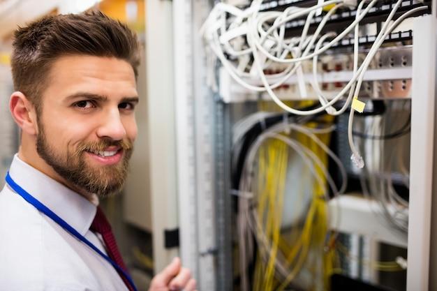 Tecnico sorridente che sta in una stanza del server