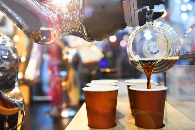 Tecnologia automatica in negozio di bevande, intelligenza artificiale, braccio robotico che serve in caffetteria