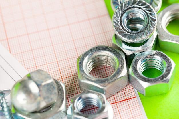 Tecnologia e lavorazione dei metalli. bullone e dado in metallo su disegni stampati