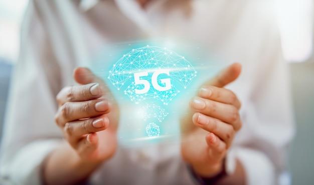 Tecnologia futura rete 5g, mani che tengono interfaccia schermo reti di nuova generazione ad alta velocità. sistemi wireless e internet of things (iot).