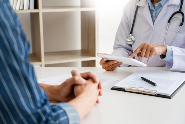 Tecnologia in medicina e assistenza sanitaria, consultazione con il medico discutere i record con il paziente utilizzando la tavoletta digitale nell'ufficio del medico