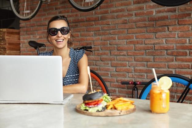 Tecnologia moderna e concetto di comunicazione. free lance graziose della donna in occhiali da sole che lavorano a distanza sul computer portatile generico che si siede alla tavola con succo d'arancia e l'hamburger freschi